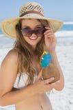 Recht blond im weißen Bikini, der Kokosnussgetränk auf dem Strand hält Stockfoto
