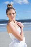 Recht blond im weißen Kleid, das auf dem Strand aufwirft Lizenzfreies Stockfoto