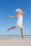 Recht blond im weißen Kleid, das auf den Strand springt Lizenzfreies Stockfoto