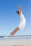 Recht blond im weißen Kleid, das auf den Strand springt Lizenzfreies Stockbild
