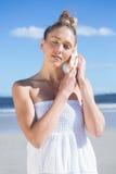 Recht blond im weißen Kleid, das auf Tritonshorn auf dem Strand hört Lizenzfreie Stockfotografie
