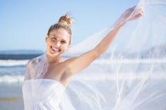 Recht blond im weißen Kleid, das Schal auf dem Strand hält Stockfotografie