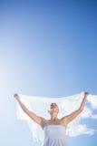 Recht blond im weißen Kleid, das Schal auf dem Strand hält Stockbild