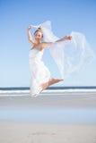 Recht blond im weißen Kleid, das Schal auf dem Strand hält Stockfotos