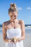Recht blond im weißen Kleid, das Starfish auf dem Strand hält Stockfoto