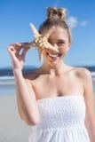 Recht blond im weißen Kleid, das Starfish auf dem Strand hält Stockfotos