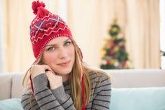 Recht blond im Winter kleidet das Sitzen auf der Couch Stockbild