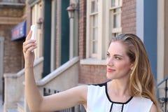 Recht blond mit dem langen Haar nimmt selfies mit ihrem Smartphone Lizenzfreies Stockfoto