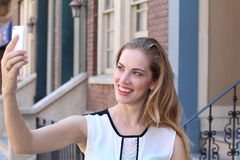Recht blond mit dem langen Haar nimmt selfies mit ihrem Smartphone Lizenzfreie Stockfotografie