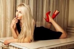 Recht blond mit dem Verführungsblick, der auf Tabelle liegt Stockfotografie