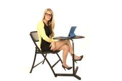 Recht blond mit den Gläsern, die am Schreibtisch mit den Beinen gekreuzt sitzen Stockfotografie