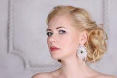 Recht blond mit Frisur und in den Ohrringhaltungen Stockfotos