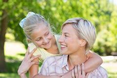 Recht blond mit ihrer Tochter im Park Stockbild
