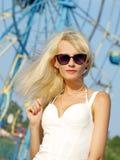 Recht blond mit Sonnenbrillen gegen Karussell. Stockfoto