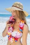 Recht blond in nippendem Cocktail der Blumengirlande auf dem Strand Lizenzfreies Stockbild