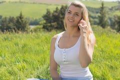 Recht blond am Telefon, das auf Gras sitzt Lizenzfreie Stockfotografie