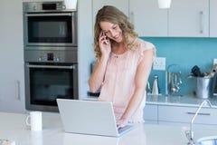 Recht blond am Telefon unter Verwendung des Laptops Lizenzfreies Stockbild