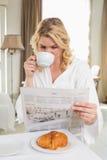 Recht blond in trinkendem Kaffee des Bademantels und in Ablesenzeitung Stockfotos