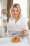 Recht blond in trinkendem Kaffee des Bademantels und in Ablesenzeitung Lizenzfreie Stockfotos