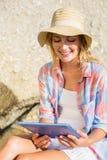 Recht blond unter Verwendung des Tabletten-PC am Strand Lizenzfreie Stockfotografie
