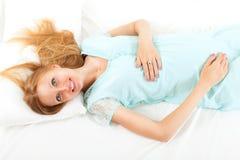 Recht blond wacht in ihrem Bett auf Lizenzfreie Stockfotos