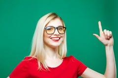 Recht blond zeigt sich durch Finger und lächelt auf grünem Hintergrund Porträt des schönen Mädchens im Studio Stockfotografie