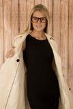 Recht blonde Aufstellung mit offenem Mantel und tragenden Gläsern Stockfoto