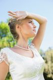 Recht blonde Braut, die Arm zur Stirn am sonnigen Tag hält Stockbild