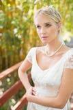 Recht blonde Braut, die auf einer Brücke steht Lizenzfreie Stockfotografie