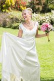 Recht blonde Braut, die Blumenstrauß und ihr Kleid hält Stockbilder