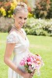 Recht blonde Braut, die den Lilienblumenstrauß lächelt an der Kamera hält Stockfotografie