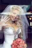 Recht blonde Braut, die durch das Fenster schaut Stockfotografie