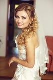 Recht blonde Braut mit dem langen Haar lächelt, schauend über ihrem shoul Stockfotografie