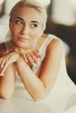 Recht blonde Braut sitzt gelehnt auf einem Klavier, das ihr Gesicht mit hält Stockbild
