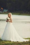 Recht blonde Braut steht auf dem Seeufer an einem glänzenden Tag Lizenzfreie Stockfotos