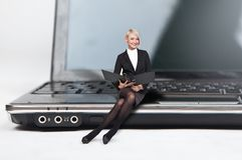 Recht blonde Dame, die auf einem Laptop sitzt Lizenzfreies Stockbild