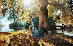 Recht blonde Dame, die im Herbstwald aufwirft Stockfotos