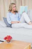 Recht blonde Entspannung auf Couch und Lesebuch Lizenzfreie Stockfotografie