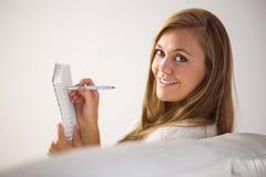 Recht blonde Entspannung auf dem Couchschreiben im Notizblock Lizenzfreie Stockfotos