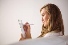 Recht blonde Entspannung auf dem Couchschreiben im Notizblock Stockfoto