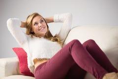 Recht blonde Entspannung auf der Couch Lizenzfreie Stockfotografie
