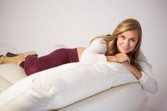 Recht blonde Entspannung auf der Couch Stockfotos