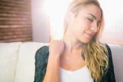 Recht blonde Entspannung auf der Couch Stockbild