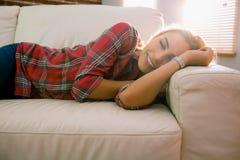 Recht blonde Entspannung auf der Couch Lizenzfreies Stockfoto