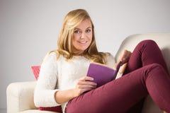 Recht blonde Entspannung auf der Couch mit Buch Lizenzfreie Stockbilder