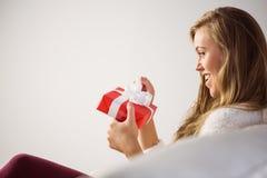Recht blonde Entspannung auf der Couch mit Geschenk Stockbild