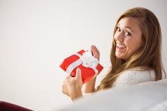 Recht blonde Entspannung auf der Couch mit Geschenk Stockfoto