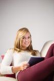 Recht blonde Entspannung auf der Couch mit Tablette Stockfotos