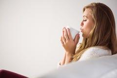 Recht blonde Entspannung auf der Couch mit Tee Stockfoto