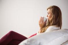 Recht blonde Entspannung auf der Couch mit Tee Lizenzfreie Stockfotografie